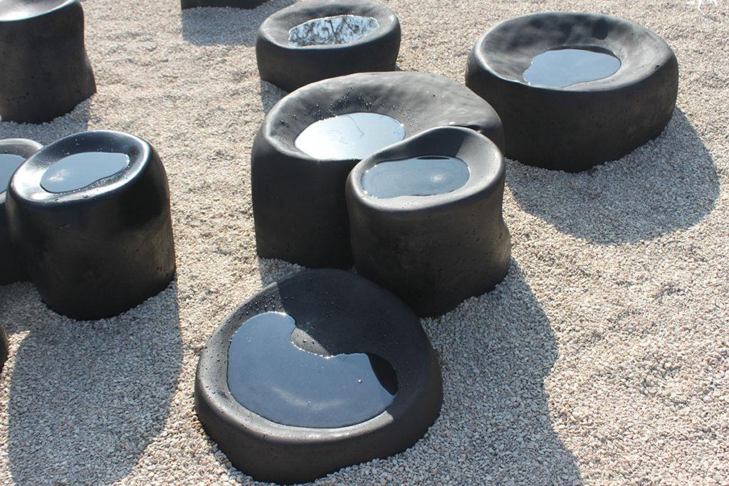 Cupules - 26 éléments en béton gris sombre, gravillon clair, dans le bassin de rétention.
